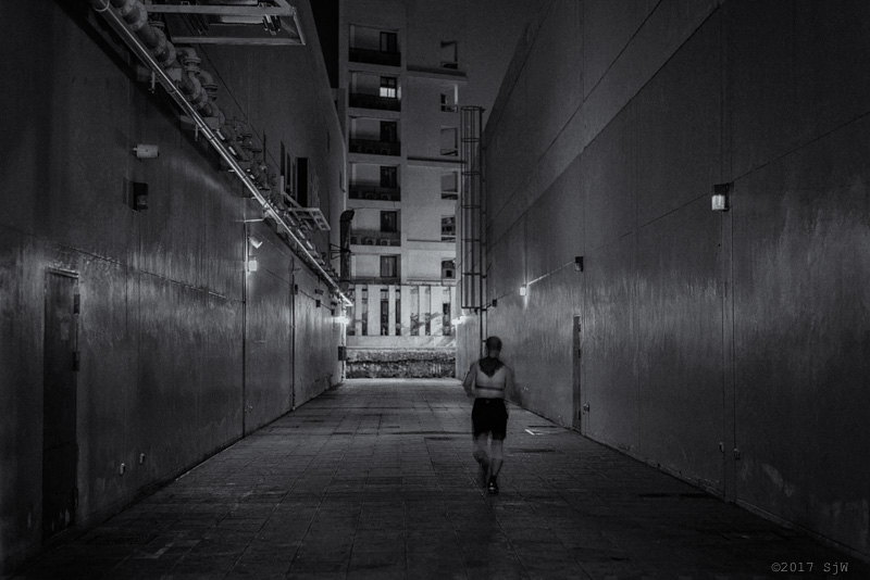 Man running in an alley at night