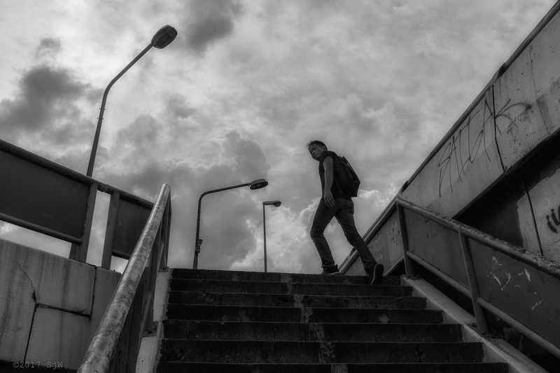 Man climbing the steps of the overpass at Lat Phrao in Bangkok