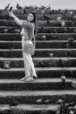 Young woman with mobile phone on the riverside steps of Wat Rakhang in Bangkok