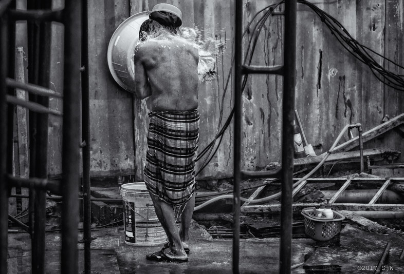 Man bathing after a day's work on a building site in Bangkok