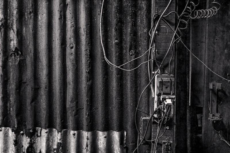 Electrical switch and wiring on a wall of rusted corrugated iron in Bangkok
