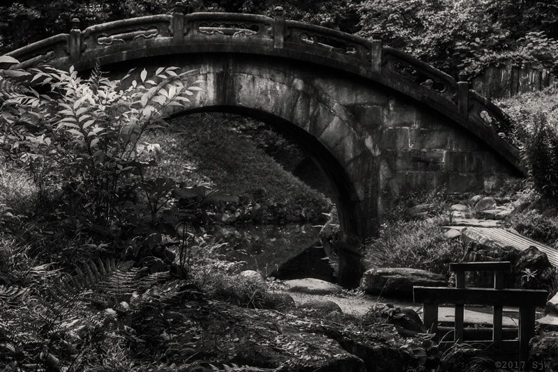 Stone bridge over a stream in Koishikawa Korakuen Garden