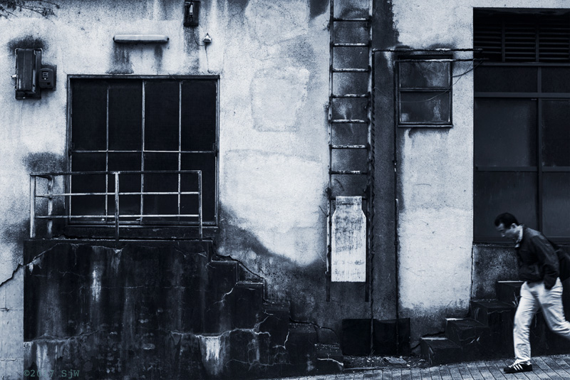 Man walking past a derelict building