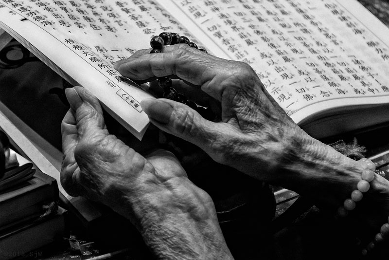 Hands turning page of a chanting book