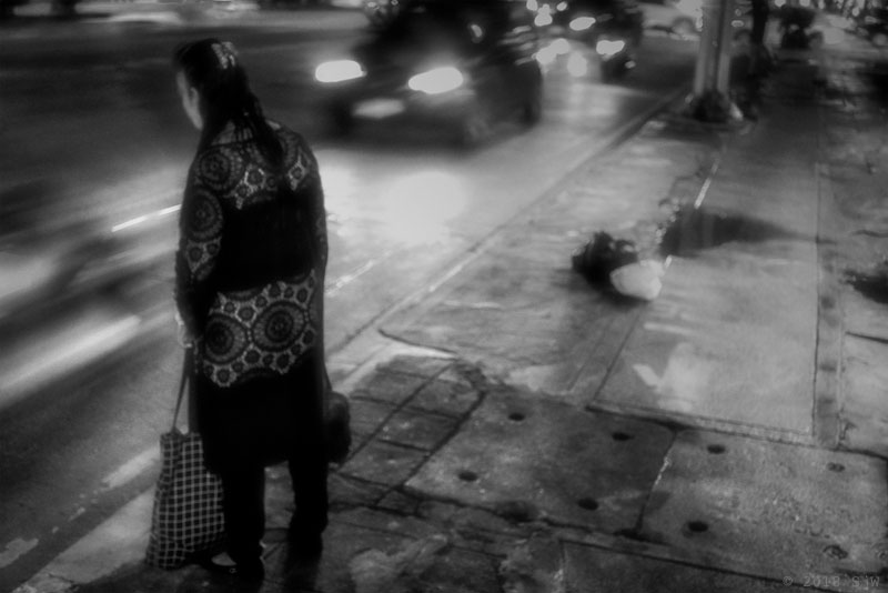 Woman waiting by the kerbside in Bangkok