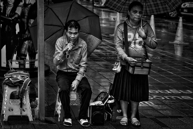 Blind people busking in the rain in Bangkok