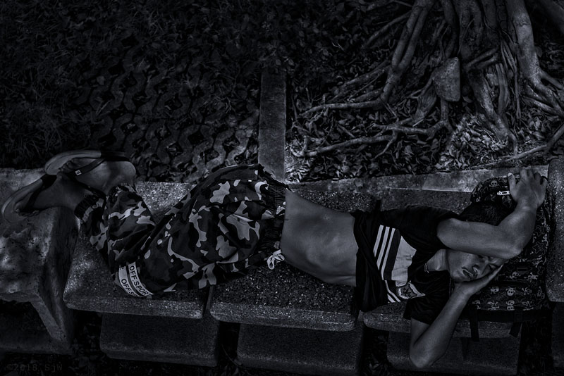 Man sleeping on a park bench in Bangkok